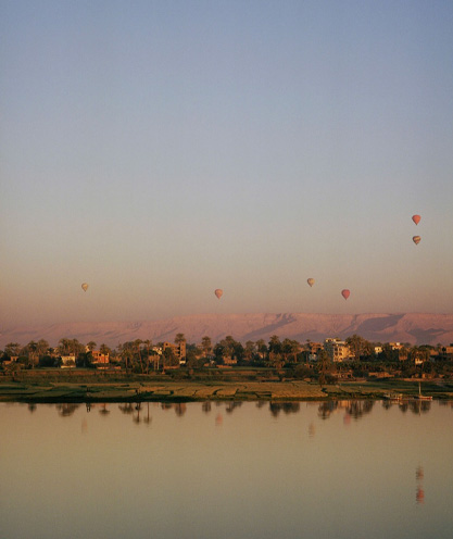 hot-air-balloons-seen-rising-at-sunset-from-across-the-nile-river