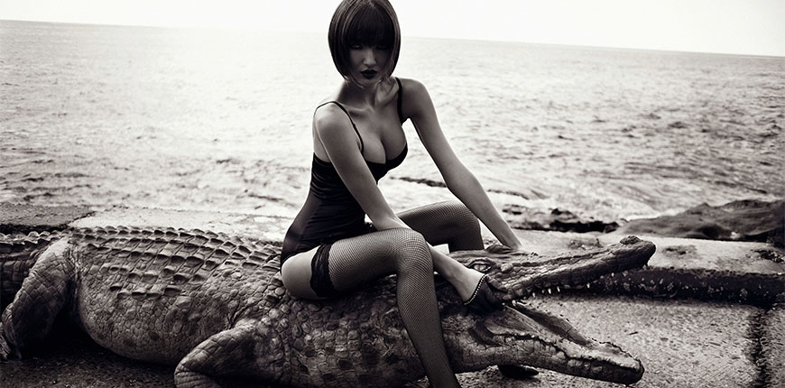black-and-white-photo-of-woman-with-bob-hair-cut-in-fiahnets-sitting-on-a-fake-crocodile