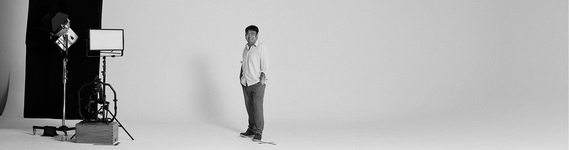 black-and-white-portrait-of-writer-director-and-cinematographer-david-tran-on-awhite-background-with-cinema-camera-and-lighting