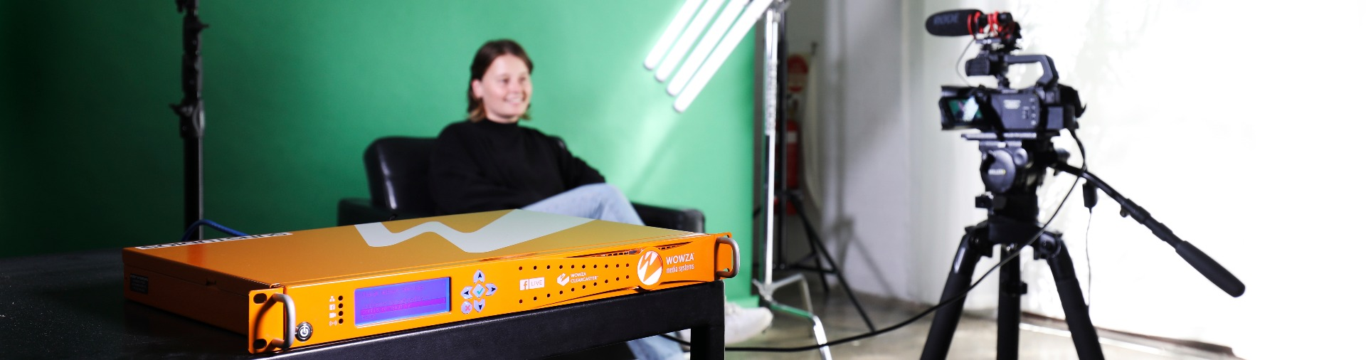 woman-sitting-in-front-of-a-green-screen-being-filmed-under-lighting-wowser-clearcaster-live-streaming-device-in-foreground