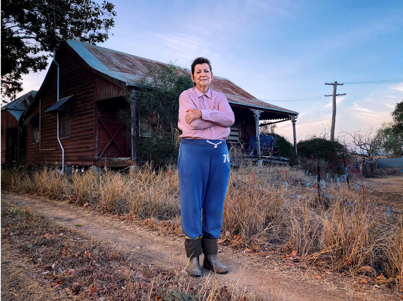 rural-woman-with-house-behind-her
