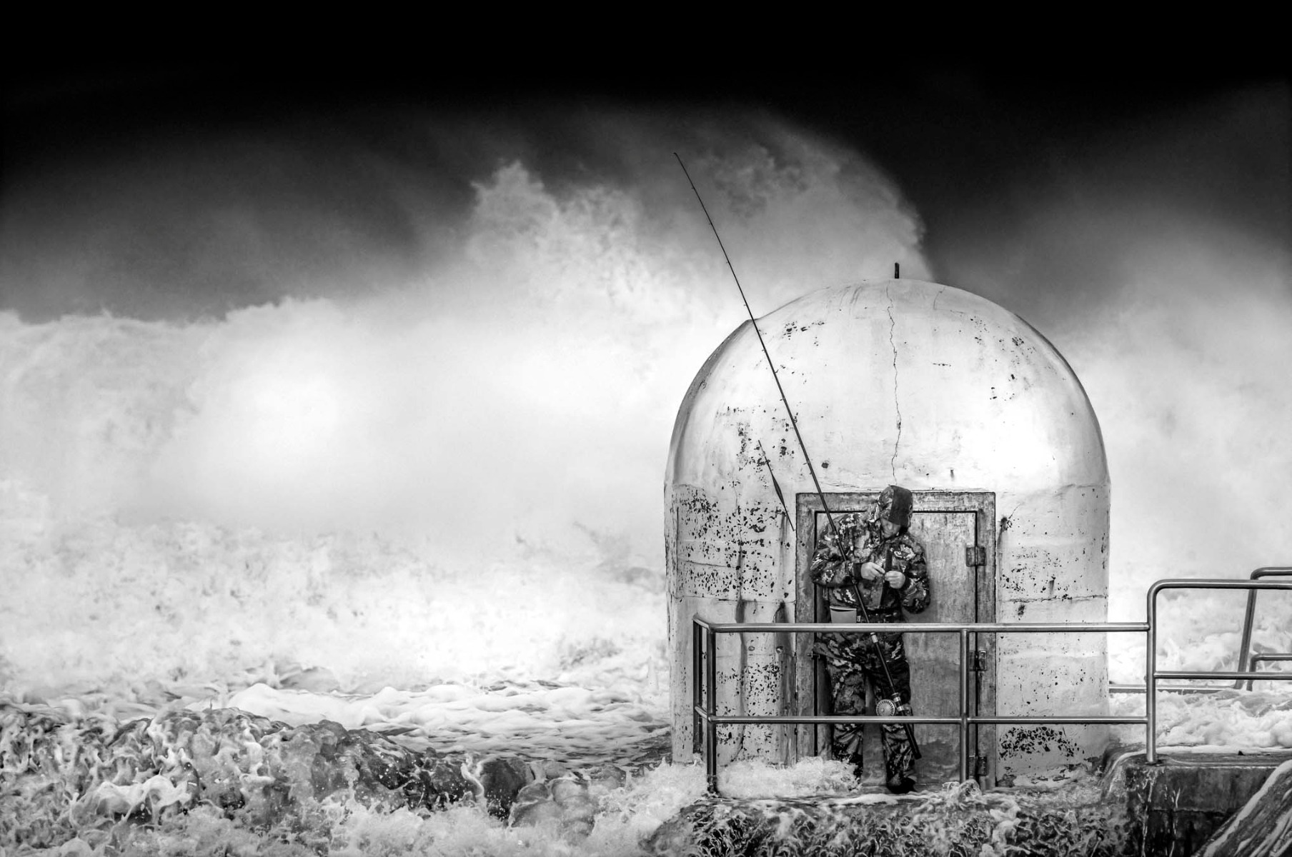 black-and-white-photograph-of-man-fishing-admist-turbluent-ocean