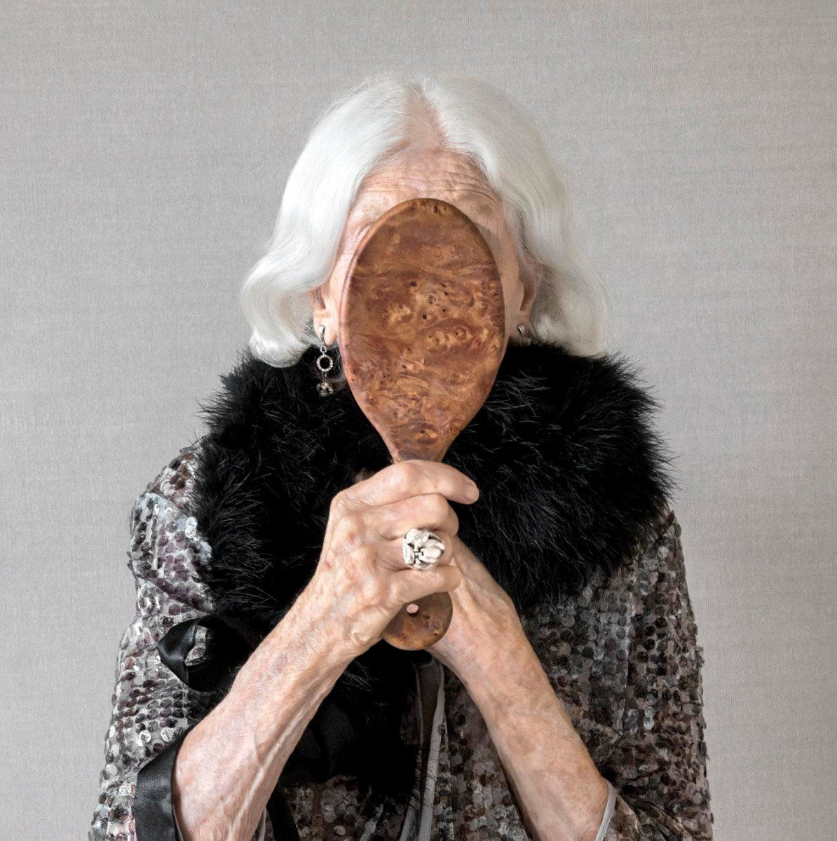 elderly-woman-holds-ornate-mirror-over-her-face