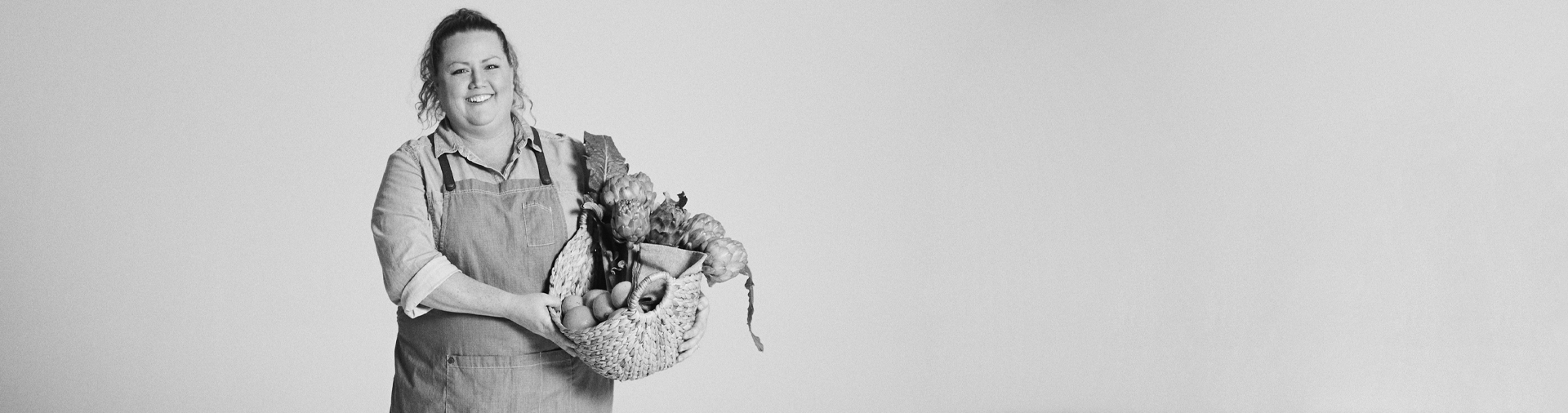 black-and-white-image-of-natalie-jaeger-holding-basket-of-produce-by-kristina-yenko