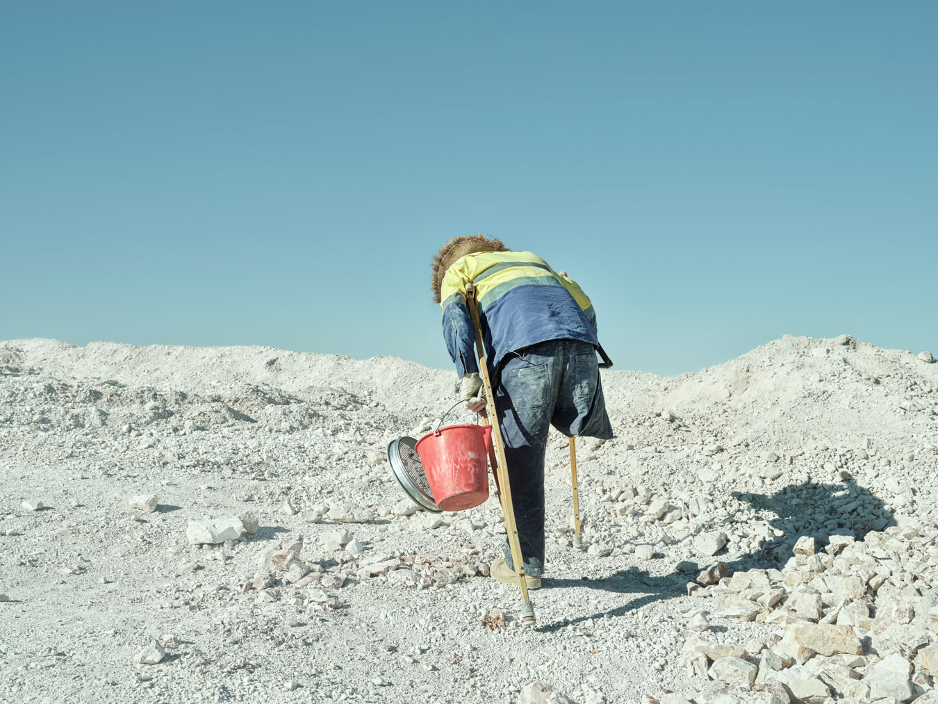 man-from-behind-climbing-dusty-terrain-with-crutches