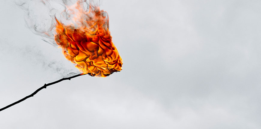detailed-photograph-of-stick-burning-against-grey-background