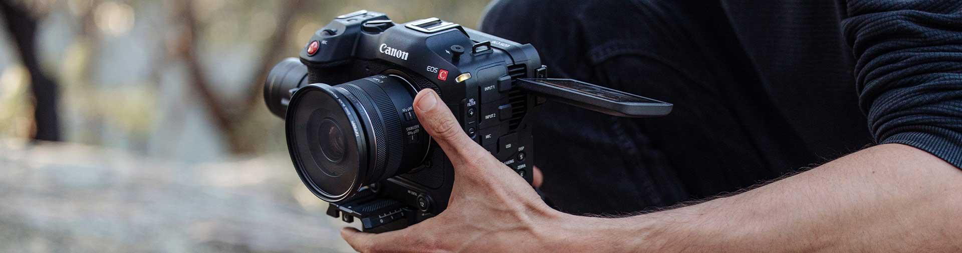 canon-eos-c70-cinema-body-in-hands-against-bush-backdrop