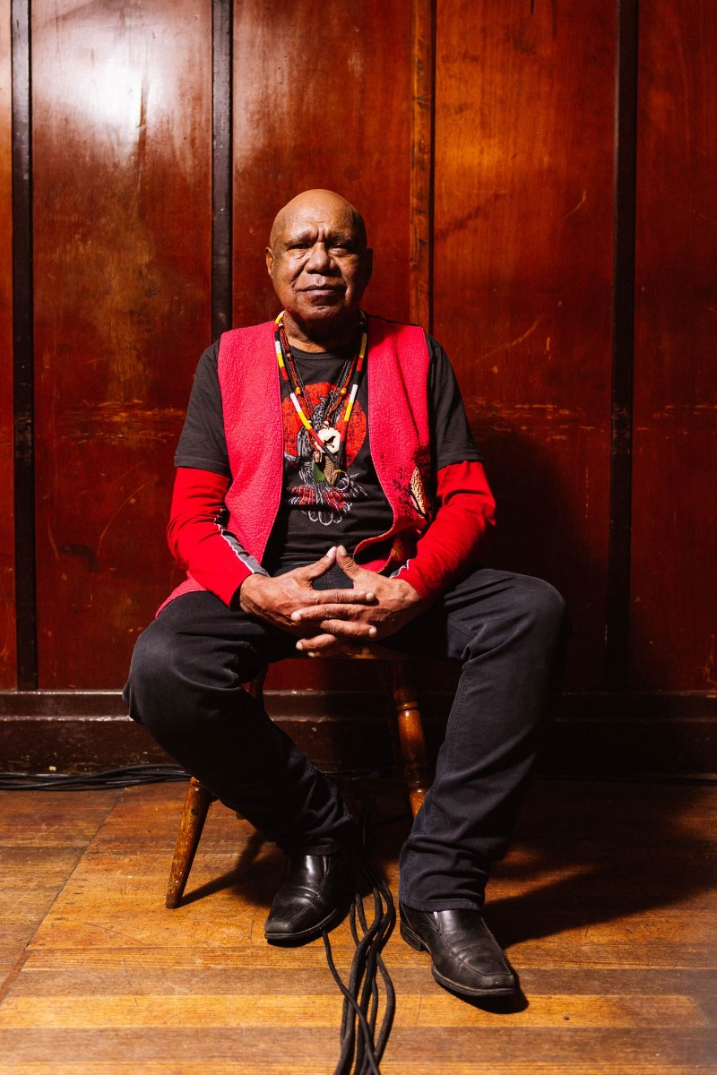 musican-archie-roach-against-a-wooden-panel-wall-in-a-red-vest