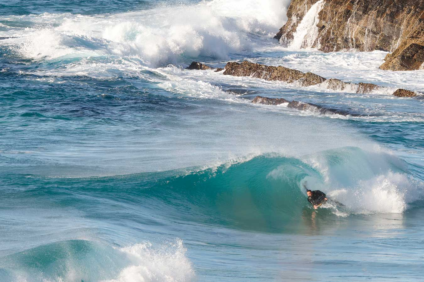 surfer-mid-aqua-wave-curl-with-rocks-in-background
