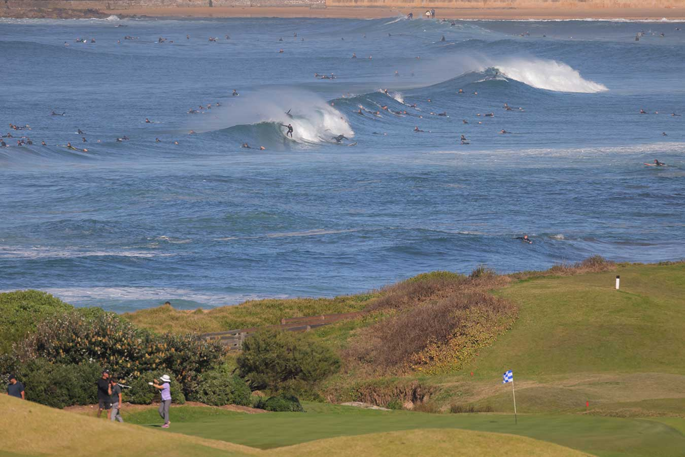 golfers-on-rolling-hills-in-foreground-many-surfers-on-olling-waves-in-background