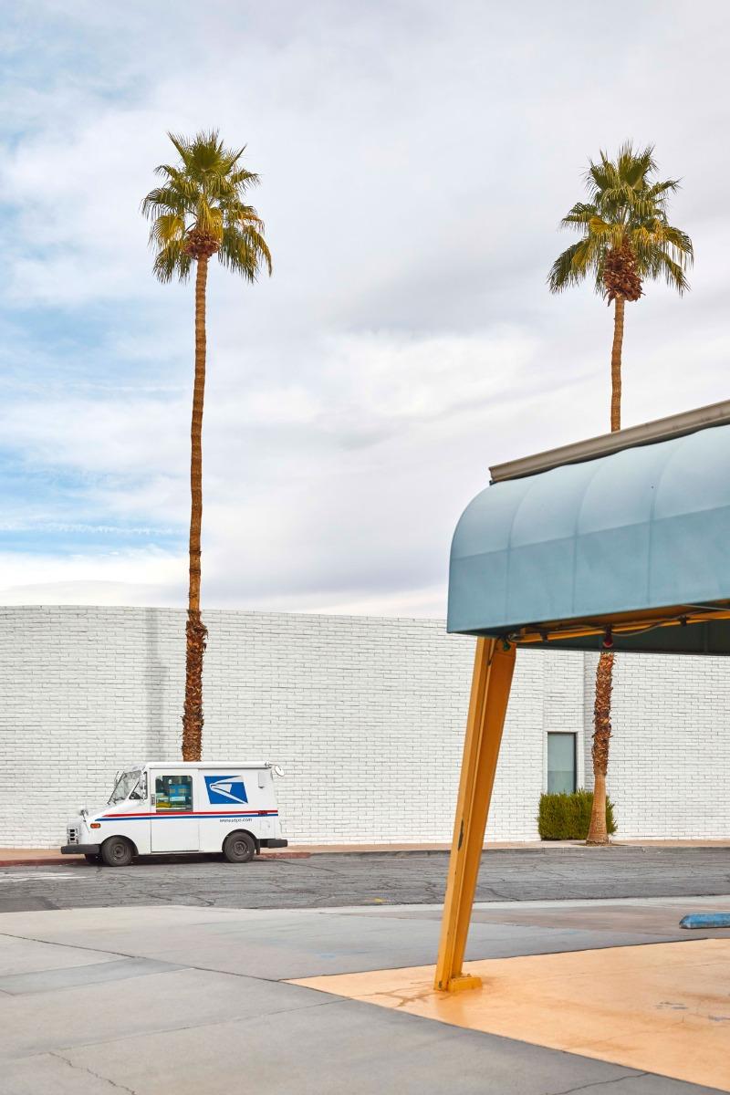 usps-van-parked-in-bright-urban-landscape-near-a-palm-tree