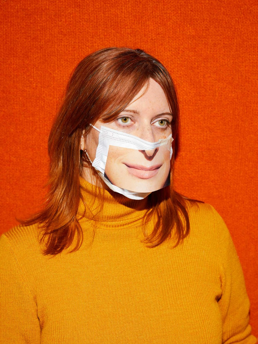 self-portrait-of-photogrpaher-nicole-reed-against-orange-background-with-facemask-carrying-a-photo-of-a-smile