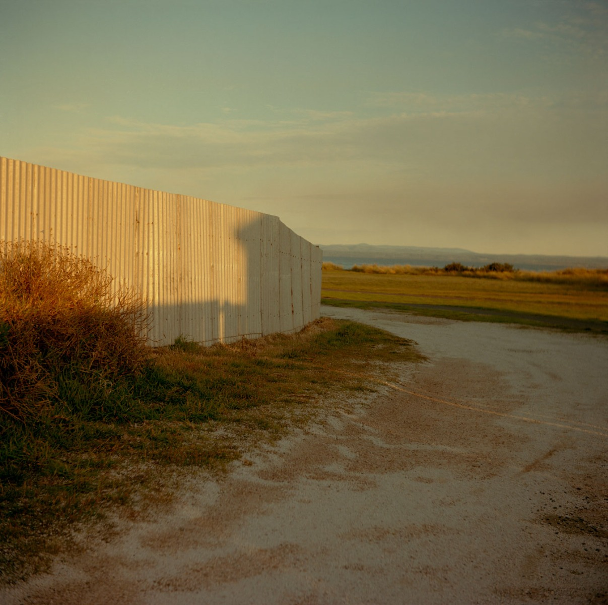 afternoon-light-casts-a-house-shaped-shadow-on-an-iron-fence-in-rural-australia