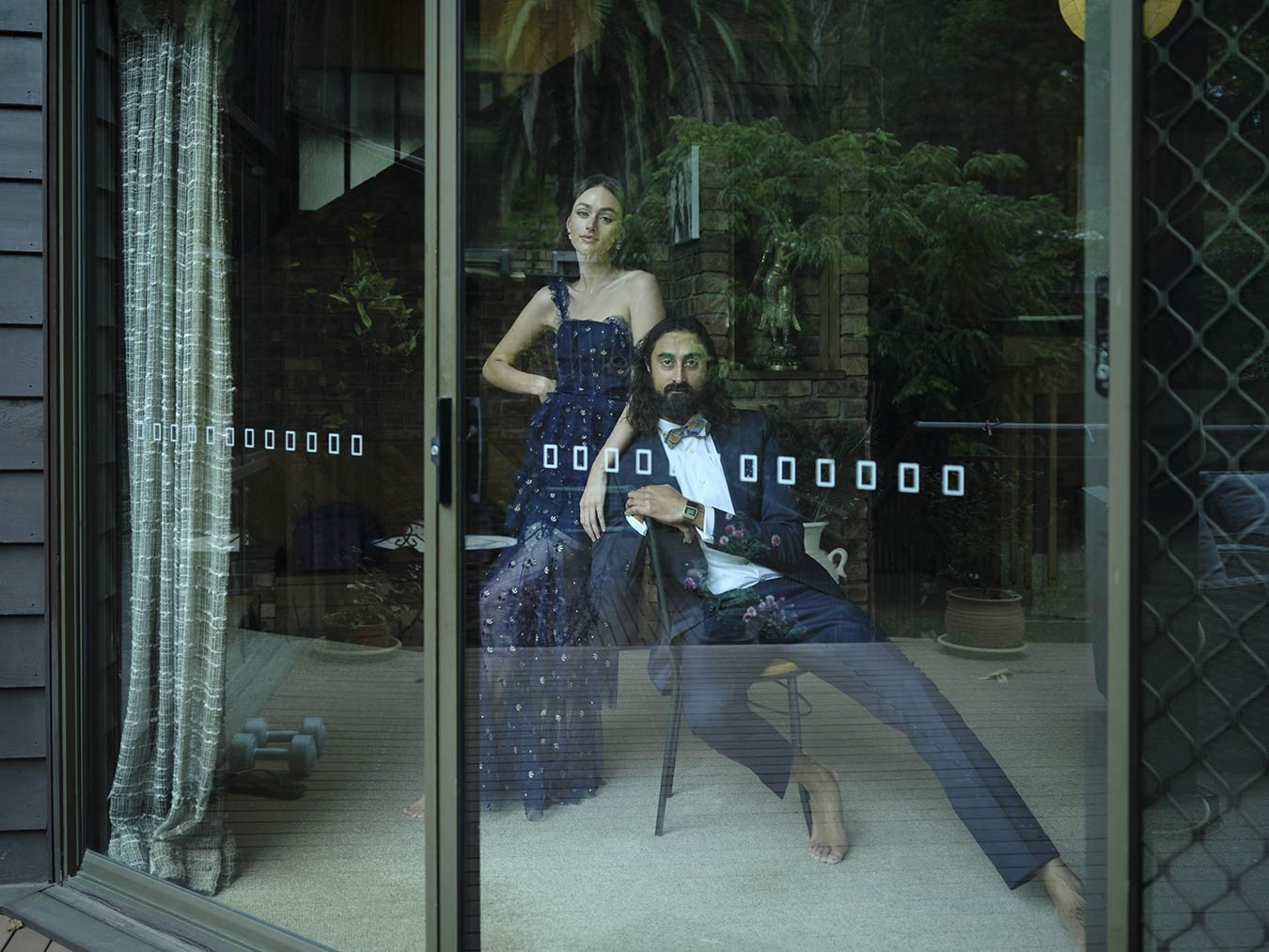 man-andwoman-behind-glass-door-dressed-formally-in-domestic-setting-without-shoes