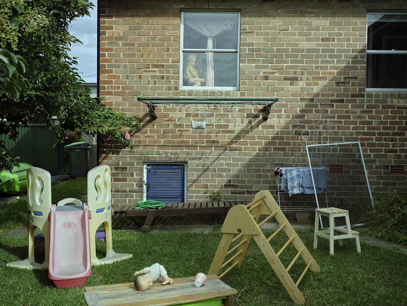 backyard-with-scattered-toys-woman-and-child-in-window