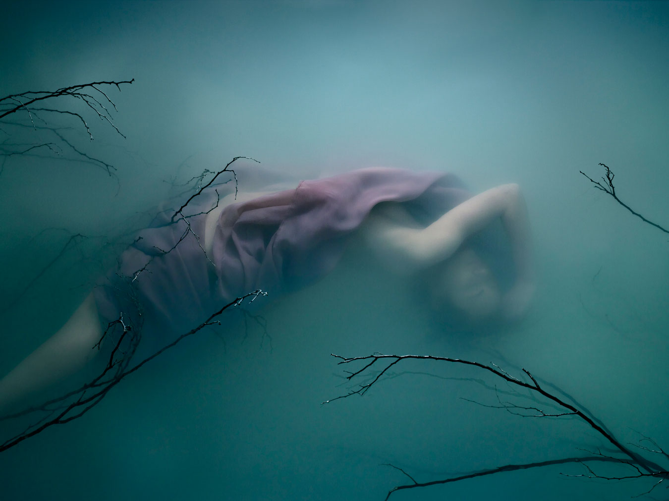 anonymous-woman-draped-in-pink-cloth-submerged-under-milky-turquoise-water