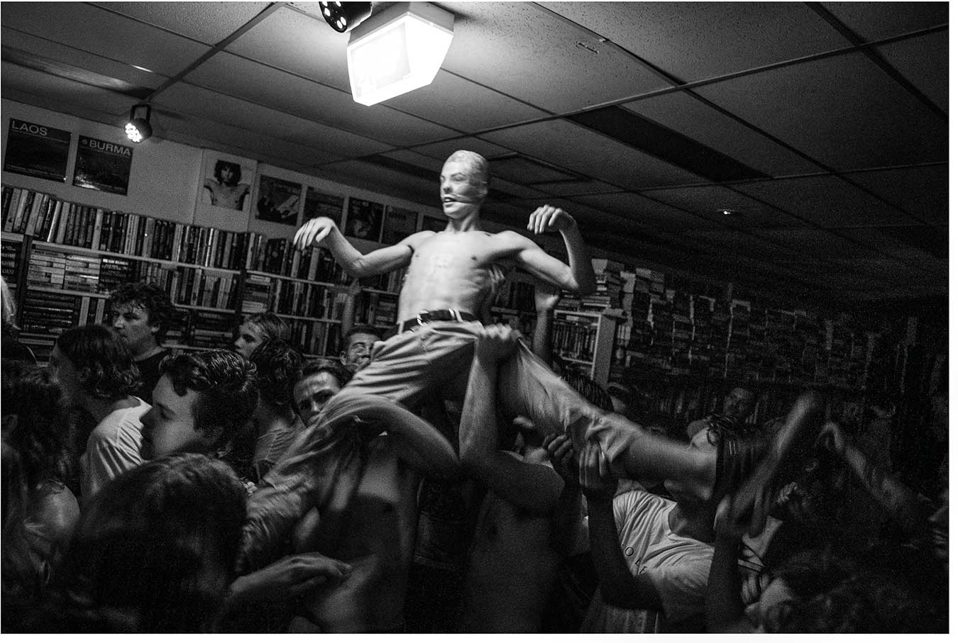 black-and-white-photo-of-a-man-with-a-stocking-pulled-over-his-head-at-a-music-performance-in-a-bookstore
