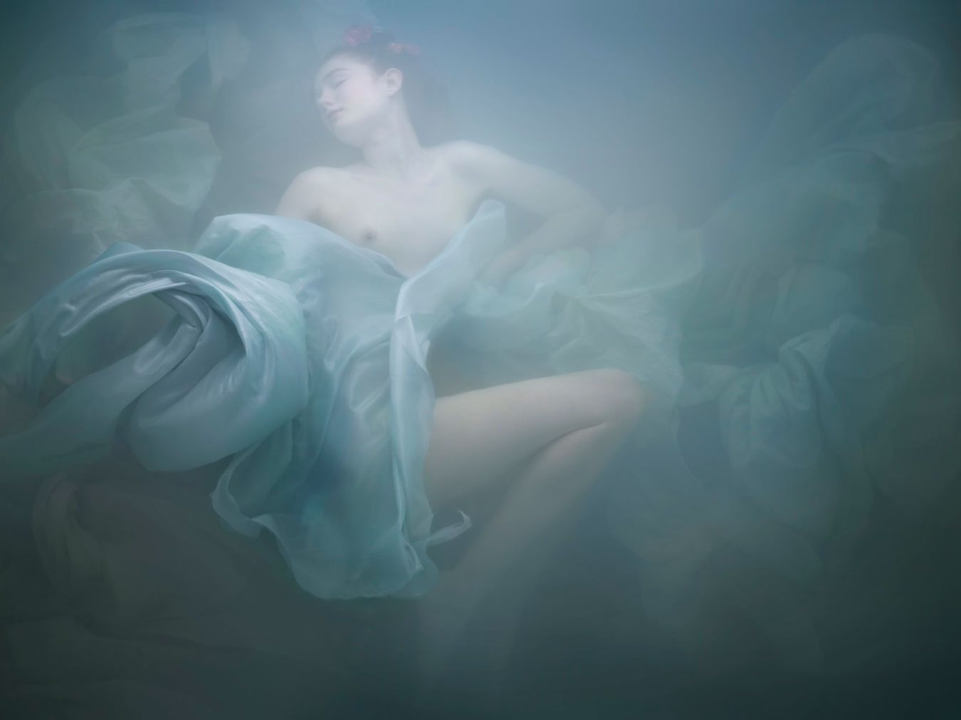 anonymous-woman-draped-in-blue-cloth-submerged-under-milky-turquoise-water