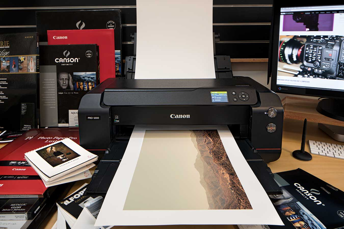 a-canon-pro-1000-printer-mid-print-of-a-landscape-surrounded-by-paper-and-inks