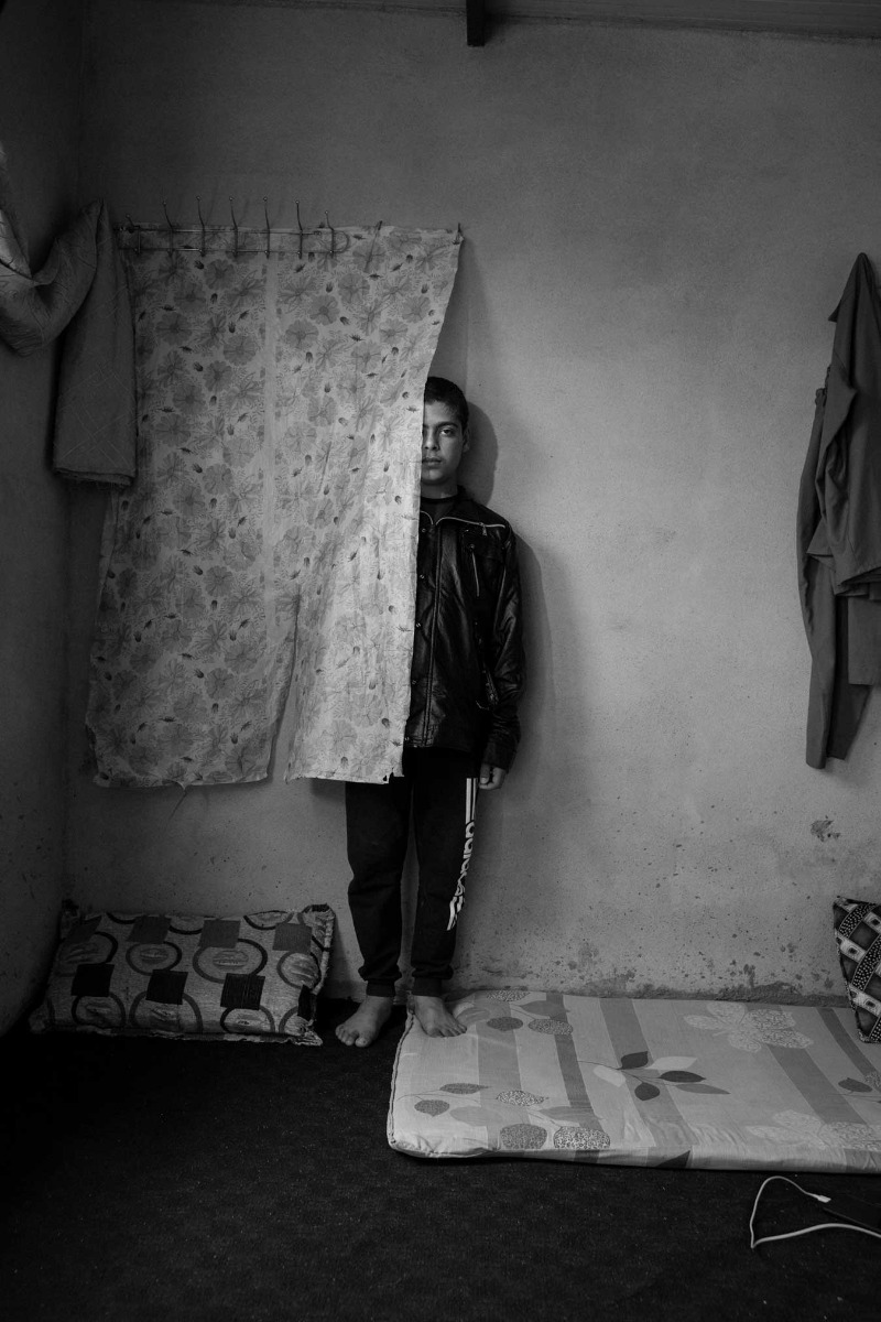 black-and-white-image-f-boy-partially-obscured-behind-wall-hanging