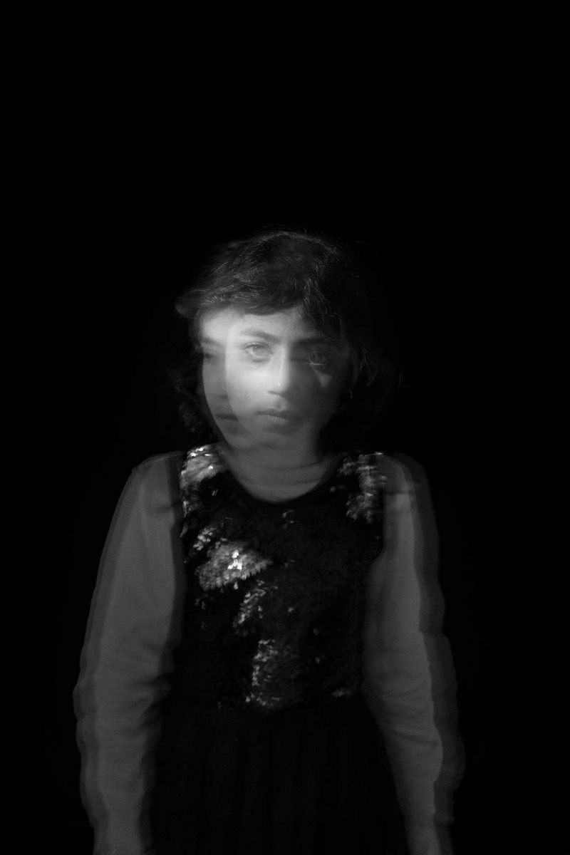 blac-and-white-image-of-girl-slight-double-exposure-showing-movement-and two-angles-to-her-head