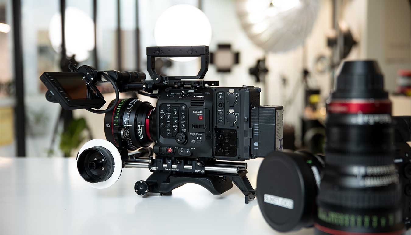 the-new-canon-c300-mark-three-with-lenses-on-a-table-with lighting-behind