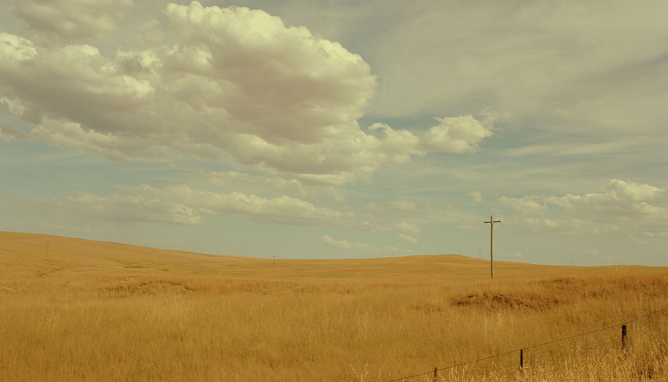 yellow-feild-of-wheat-white-clouds-and-a-power-line-looking-like-a-cross-within-the-field