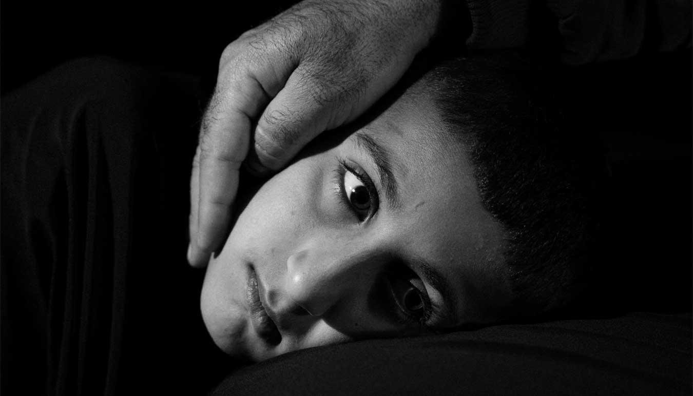 black-and-white-image-of-boy-with-reassuring-hand-over-his-cheek